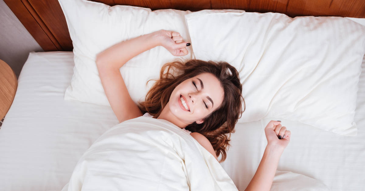 Happy woman stretching hands while lying on bed at home